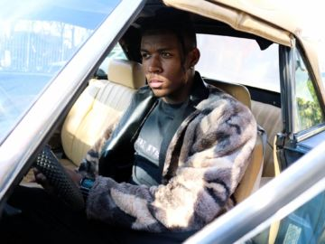 man sitting in the driver's seat of a car wearing mens faux fur coats