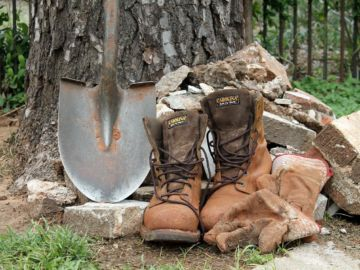 brown vegan work boots beside a tree, shovel and bricks